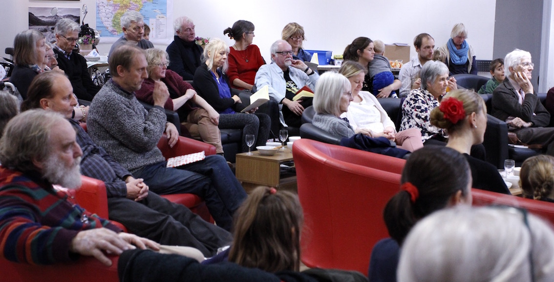 Photo shows a large crowd of people on comfy chairs in an arts centre intent on listening. That a poet is reading is implied, but it was actually Annie Fisher.