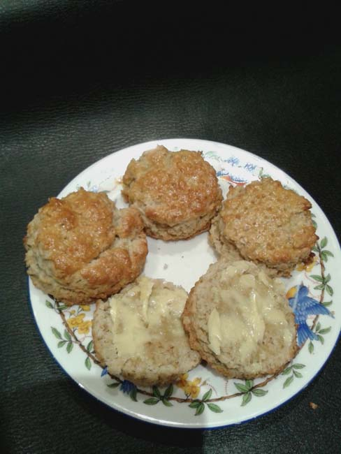 Four scones on a china plate, one cut in half and nicely spread with oozing butter. The scone must be warm!
