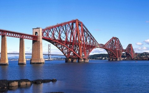 full colour picture of the Forth Railway Bridge between Fife and East Lothian. The bridge is red and could be made of meccano.