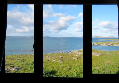 Photograph of the Hebridean coast taken through the window of Ron King's holiday house. It is divided into three sections with black frames, and is a horizontal rectangle. Through the window is amazingly turquoise see and fantastically green coastal stretches. In the sky fluffy white clouds. It looks fabulous.