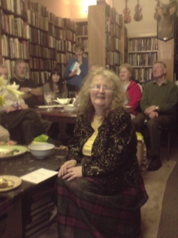 Picture of sally in the bookshop, with some oets, both seated and standing, behind her. You can also see two fiddles hanging on the walls and the singing deer -- an imitation deer's head with antlers that can produce a song if you press the right button. On the table by Sally there is a bowl of nibbles and a vase of huge lilies.