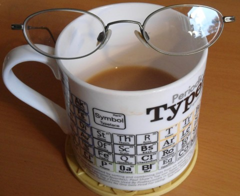 Photograph of my mainly drunk mug of tea with a pair of glasses balanced across the top. The mug is white and decorated with examples of different typefaces. You can see TYP and held of the E in bold print at the top.