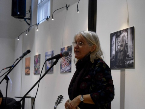 Close up of Annie reading or singing. She is wearing glasses and has shoulder length grey/blonde hair and a dark dress. She looks pretty happy and focussed.