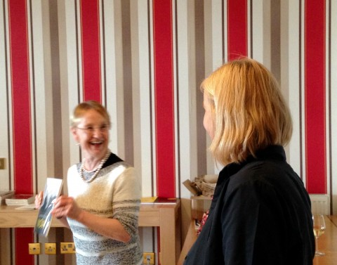 Helena Nelson and Charlotte Gann. Helena is holding up a copy of the book and laughing at some joke evidently just made by Charlotte, who is pictured (shoulder length blonde hair) from the back and in half profile. Behind them is wallpaper in thick vertical stripes of bright red, white and gold.