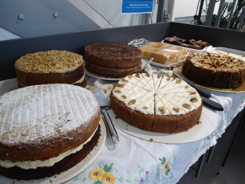 An array of cake: Victoria sponge, Walnut gateau, Lemon Drizzle, Coffee Cake, Something chocolatey etc, all carefully sliced and ready to serve.