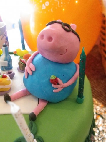 Full colour photo of Peppa Pig in marzipan sitting on a birthday cake. She is wearing classes. Behind her is what appears to be a large yellow ballon. In her hand a small carrot.