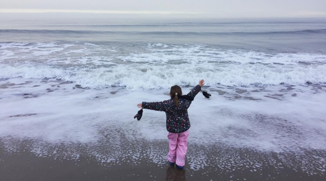 Small girl, back to camera, faces the sea flinging her arms in the air in a gesture which could be either defiant or inviting. Her trousers are waterproof and very pink.