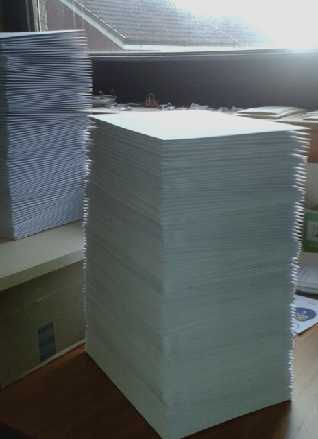 Photograph of large pile of envelopes, resembling a small skyscrap[er