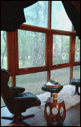 Photo shows a window or windows that take up an entire wall with a few of damp woods on the other side. There is a black leather chair (empty) in front of them, with a footstool piles with books, and a small table holding a mug of something.