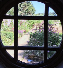 Photo shows a circular window with a lattice pattern, though which a rather lovely garden can be glimpsed with trellises and pink trailing flowers.