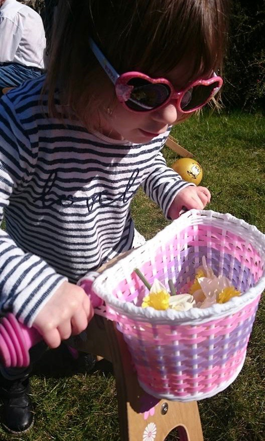 Image of small girl riding a small bike. She is wearing very large heart-shaped sunglasses and the frames are pink, like the handles and backed on her bike. The basket seems to be full of daffodil heads.