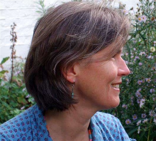 Head and shoulders colour photo of poet in profile, smiling and relaxed and looking to the right of the page. She is wearing a blue and white top, and behind her is a bank of wild flowers.