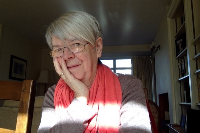 This is the poet with chin in her right hand and head slightly to one side. She is wearing glasses and has short white-grey hair. Behind her we can see most of a window, and in front of her something (perhaps another window) is throwing a wide band of light across her forearms and chest. She is wearing a salmon pink scarf looped around her next. To her left are ceiling high bookshelves.