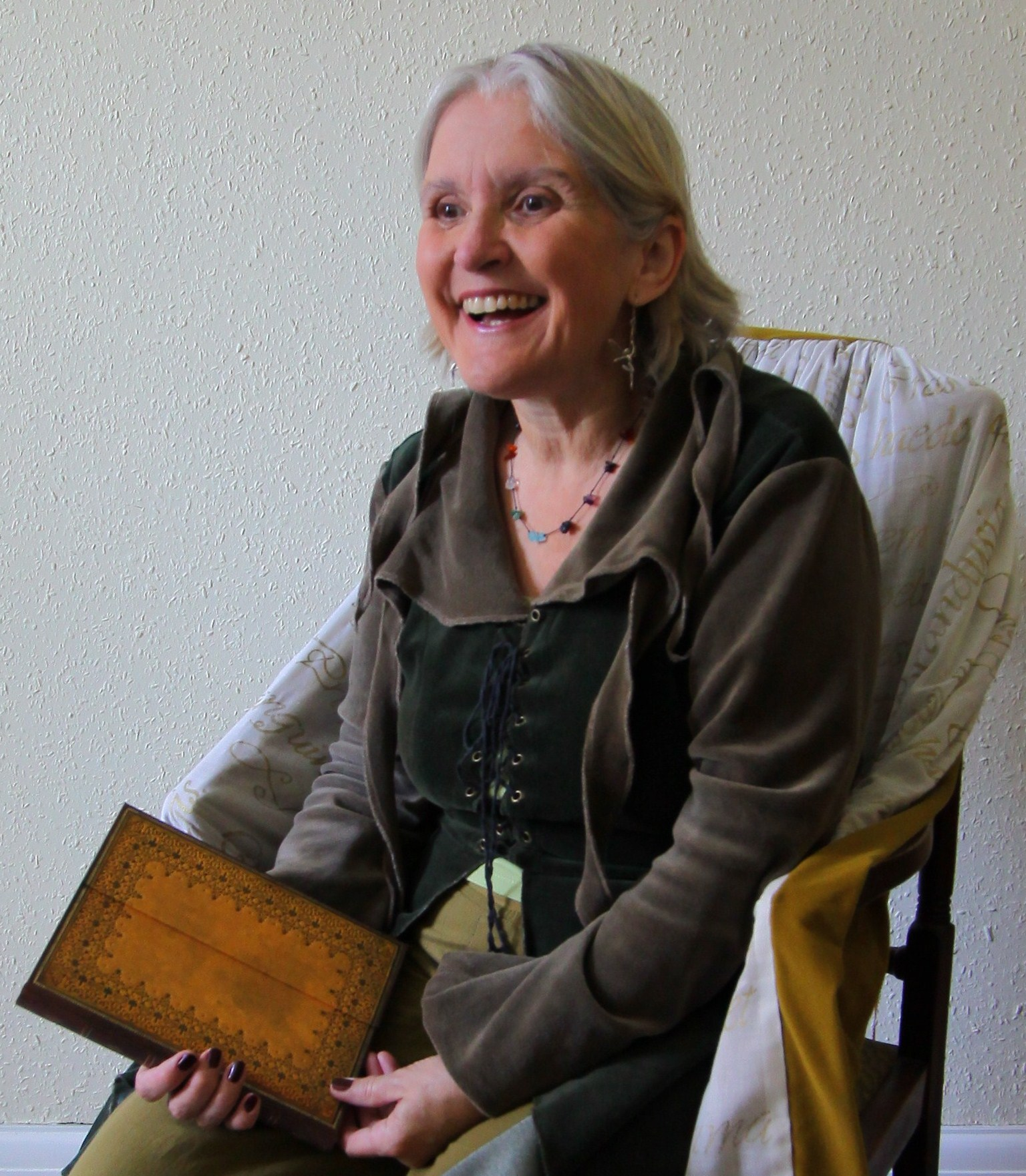 Picture of the author with a huge smile, almost a laugh of delight, an sitting on a chair with a large book in her lap.