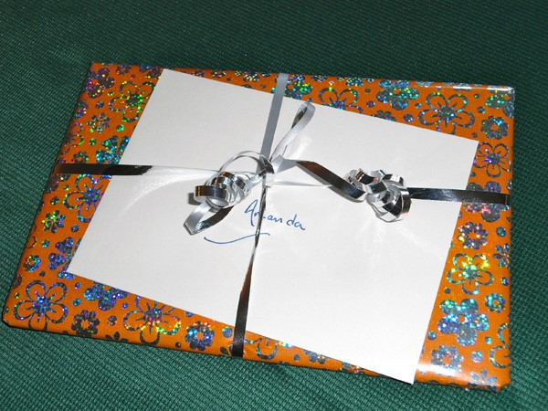 A gift wrapped in sparkly orange and silver paper with a flower motif. A whilte envelope is tucked under its silver ribbon.